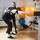 Training with ball. Couch assists women to make gymnastic ball training, supported with electric muscle stimulation Stock Photos
