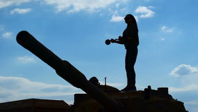 Training barbell biceps in the military. Silhouette of a slender girl, she stands on a military tank and trains on the sky background stock footage