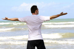 Training on the beach. Man doing breathing exercises on the beach Stock Photography