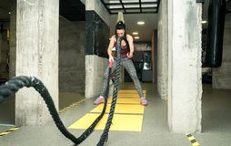 Training of beautiful young and attractive girl making serious face expression while she workout on the battle ropes in the gym. Real people workout no posing stock photography