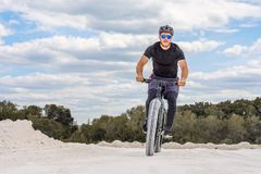 Training a bicyclist in a chalky quarry. A brutal man on a fat bike. Master. Uniform royalty free stock photos