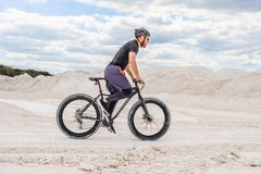 Training a bicyclist in a chalky quarry. A brutal man on a fat bike. Master. Uniform stock photos