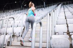 Training bij stadion, gezond wijfje die geschiktheidsoefeningen doen Wijfje die op treden lopen Royalty-vrije Stock Foto