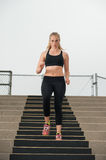 Training on bleachers in black sports bra Royalty Free Stock Photo