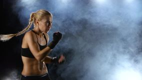 Training blows by feet strong girl boxer. Strong blows by hands with fists, beautiful blonde girl in black top and gloves on hands, side view, background with stock video footage