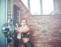 Training break. Cute sporty woman with a towel around her neck rests leaning on the barbell on background of brick wall with window in gym stock images