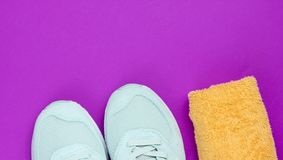 Training concept. Sport shoes, towel on a purple background. Copy space. Top view royalty free stock photos