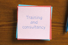 Training and consultancy written on a note Stock Photo