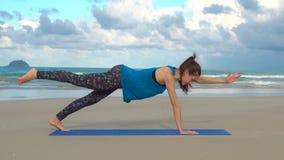 Training der jungen Frau auf dem Strand vor Meer Morgen gymnastisch Eine Bein-Plankenübung der Hand eine Gesunder Active Stockbild