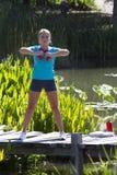 Training der jungen Frau mit Dummköpfen auf Holzbrücke und Wasser lizenzfreies stockfoto