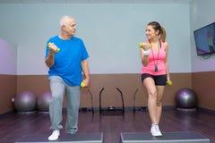 Training des älteren Mannes in der Turnhalle mit persönlichem Trainer lizenzfreie stockfotografie