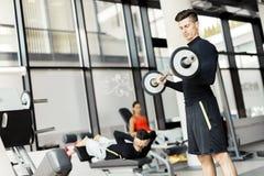 Training des jungen Mannes in einer Turnhalle Stockbild