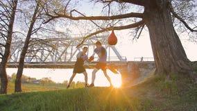 Training des jungen Mannes mit einem Trainer, Verpackenauflage, Sonnenuntergang stock footage