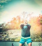 Training des jungen Mannes mit Gewichten auf der Terrasse des Hauses der Wald und der Sonnenunterganghimmelhintergrund Stockfotografie