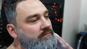 Training des Mannes für eine Rolle Santa Claus, grauhaariger Bart Vater-Frost Hipsterskys Make-upkünstler tut Make-up zu a stock footage