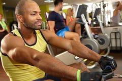 Training des schwarzen Mannes auf Rudermaschine Lizenzfreie Stockbilder