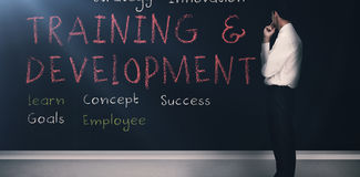 Training and development terms written on a blackboard 3d. Businessman looking at training and development terms written on a blackboard  3d Stock Images