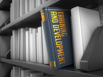 Training and Development - Title of Book. Training and Development - Gray Book on the Black Bookshelf between white ones. Educational Concept royalty free stock images