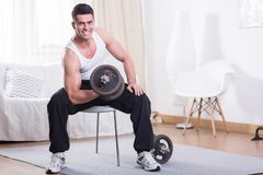Training with dumbbell. Muscular man training with dumbbell at home Royalty Free Stock Photography
