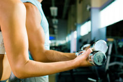 Training with dumbbells. Man and a woman (only arms and body) lifting dumbbells (focus on dumbbell, shallow depth of field Stock Photography