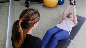 Training Eine junge Frau, die ihre ABS mit dem Trainer hält einen Dummkopf pumpt stock video