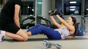 Training Eine junge Frau, die ihre ABS mit Trainer pumpt stock footage