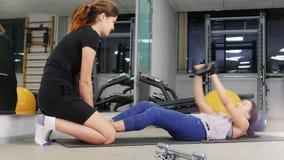 Training Eine junge Frau mit der Beinprothese, die ihre ABS mit Trainer pumpt stock footage