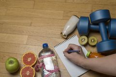 Training, exercise, cheerfulness and health - two plastic dumbbells, mineral water with juice, fruit and hand writes in a notebook. On the wooden floor. The royalty free stock images