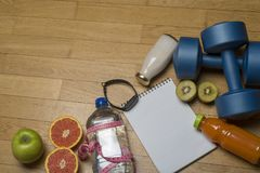 Training, exercise, cheerfulness and health - two plastic dumbbells, a notebook, mineral water with juice, fruit and a pen on the. Wooden floor. The concept of stock photo