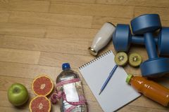 Training, exercise, cheerfulness and health - two plastic dumbbells, a notebook, mineral water with juice, fruit and a pen on the. Wooden floor. The concept of royalty free stock images
