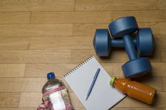 Training, exercise, cheerfulness and health - two plastic dumbbells, a notebook, mineral water with juice and a pen on the wooden. Floor. The concept of a royalty free stock image