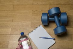 Training, exercise, cheerfulness and health - two plastic dumbbells, a notebook, mineral water and a pen on the wooden floor. The concept of a healthy stock images