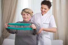 Training with exercise elastic band. Active elder lady training with exercise elastic band Stock Photography
