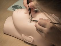 Training eyelash extensions. Work on coloring eyelashes on a mannequin. stock photos