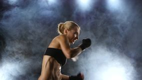 Training before the fight athletic girl boxer. Strong blows by hands with fists, beautiful blonde girl in black top and gloves on hands, side view, background stock footage