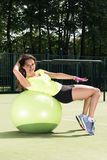 Training on the fit ball. Young woman doing sports exercises on the ball for training. Sporty appearance, a beautiful figure. Street Playground in the Royalty Free Stock Photo