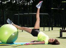 Training on the fit ball. Young woman doing sports exercises on a ball for training. Training on the fit ball. Young woman doing sports exercises on the ball for Stock Image