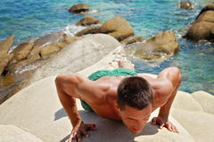 Training fitness man doing plank push up exercise outdoors against sea. Royalty Free Stock Photos