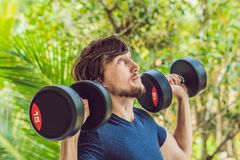 Training fitness man outside working out arms lifting dumbbells doing biceps curls. Male sports model exercising. Outdoors as part of healthy lifestyle Stock Photos