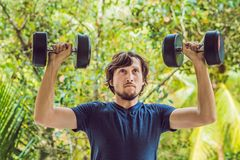 Training fitness man outside working out arms lifting dumbbells doing biceps curls. Male sports model exercising. Outdoors as part of healthy lifestyle Royalty Free Stock Images