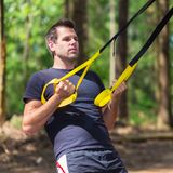 Training with fitness straps outdoors. Stock Photo