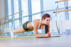 Training fitness woman doing plank core exercise working out for back spine and posture Concept pilates sport.  royalty free stock images