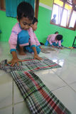 Training Folding Clothes. Children try to fold clothes while training provided by the teacher at the school in Solo, Central Java, Indonesia. The training is to Royalty Free Stock Photo