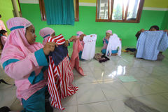 Training Folding Clothes. Children try to fold clothes while training provided by the teacher at the school in Solo, Central Java, Indonesia. The training is to Royalty Free Stock Images