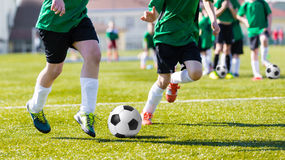 Training and football match between youth soccer teams. Young bo. Hard competition between soccer players running and kicking soccer ball. Final game of football Royalty Free Stock Images