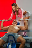 Training in the gym. Female trainer helping guy to train in the gym Bar Bench Press Stock Photo