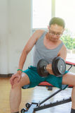 Training in the gym. Asia man middle aged training dumbbell in the gym for strength, weight loss Stock Photo