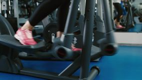 Training in the gym on the elliptical trainer feet.  stock video