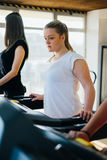 Training in the gym. Fitness girl burning calories on the treadmill. Fitness trainer doing cardio workout Stock Images
