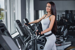 Training in the gym. Fitness girl posing and showing her figure. Fitness coach rests on the Step machine after training. Sport model posing in a sports suit Stock Photos